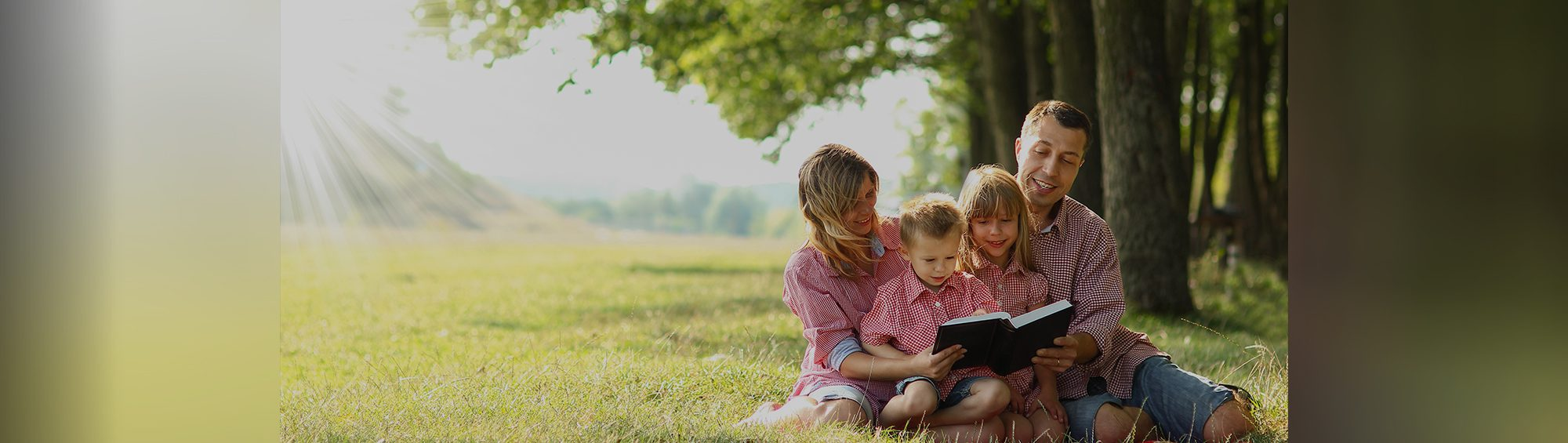 family outside reading under a tree