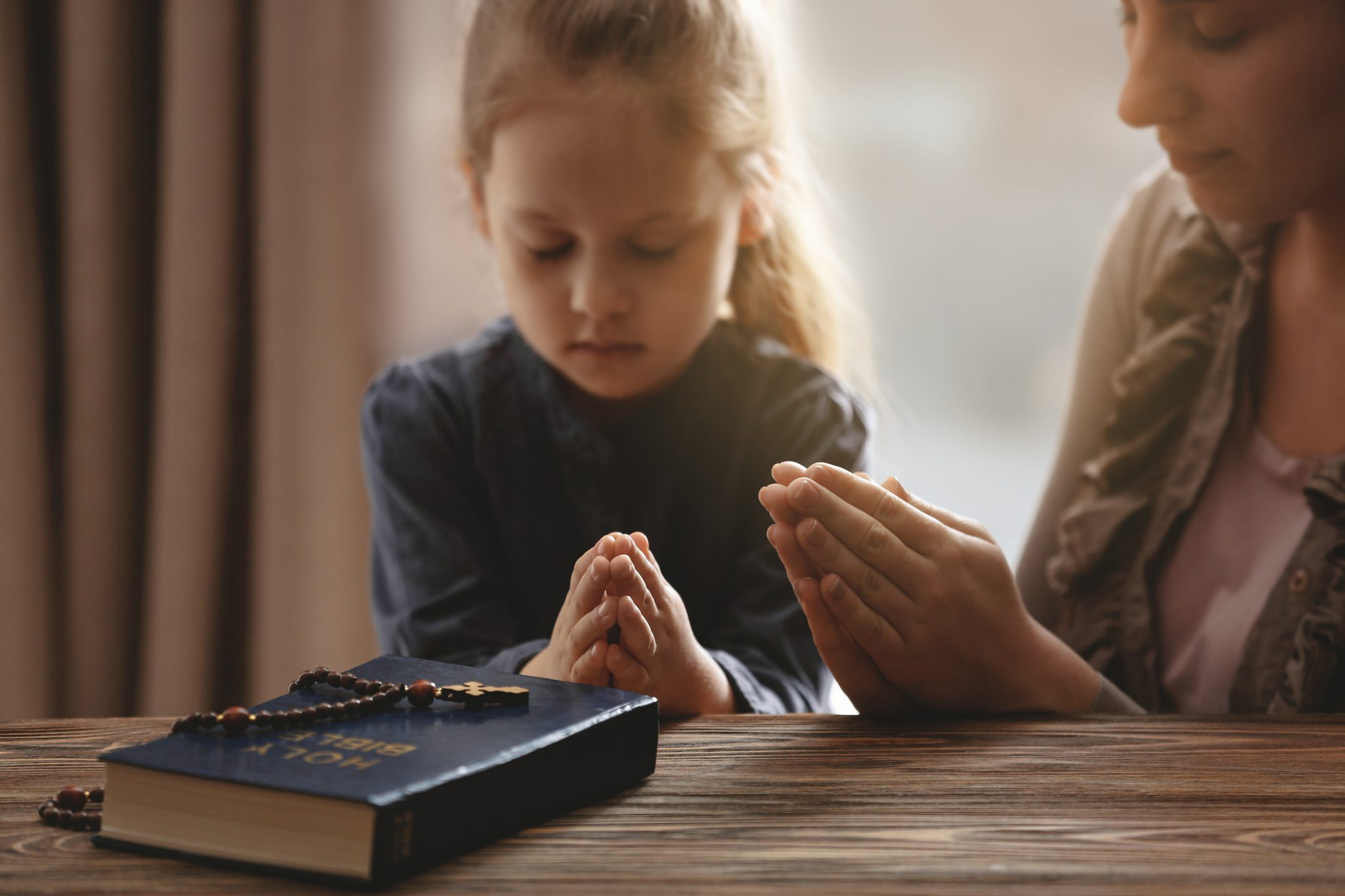 Religious Christian girl praying with her mother indoors