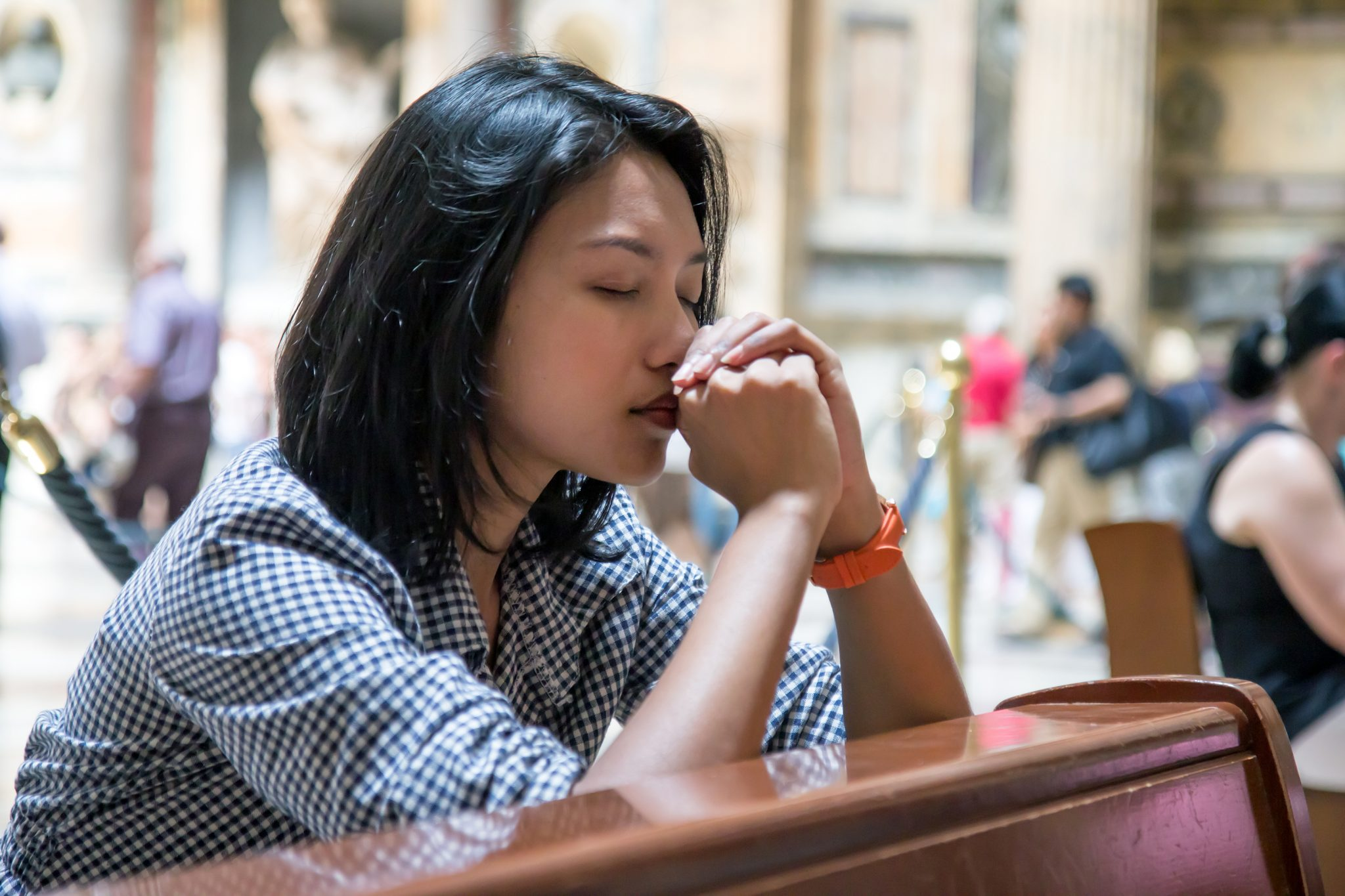 Woman praying in the church. Believers meditates in the cathedral. Spiritual time of prayer.